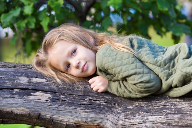 Adorable little girl on big tree in beautiful autumn park