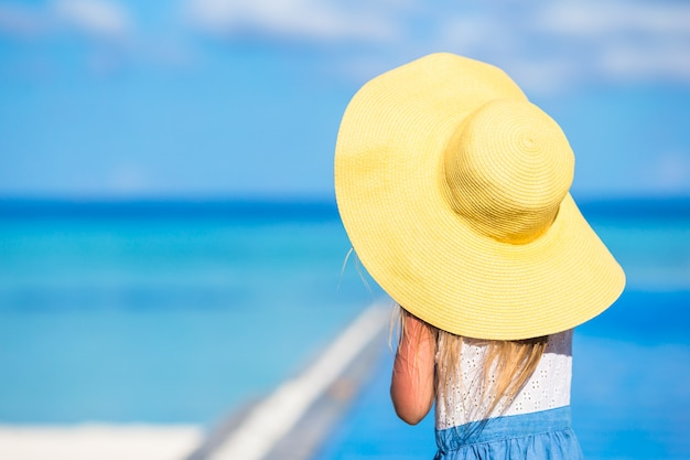 Adorable little girl at big yellow hat during summer vacation