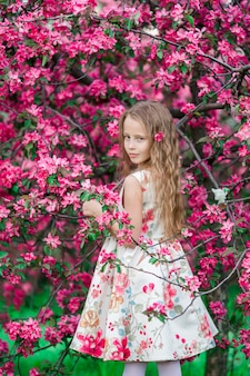 Adorable little girl in blooming spring apple garden outdoors