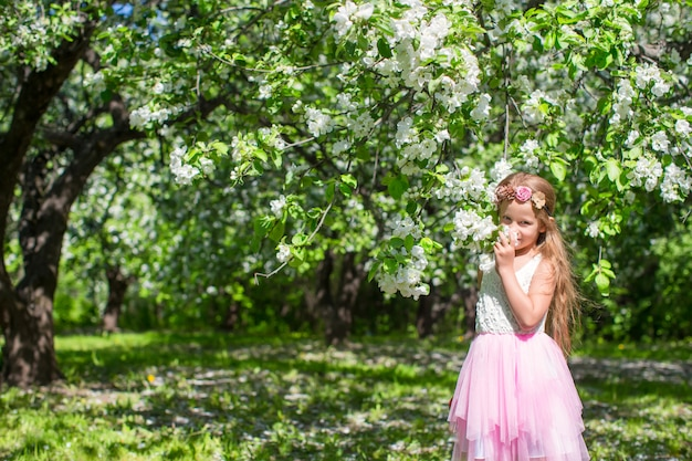 Adorable little girl in blossoming apple orchard at sunny day