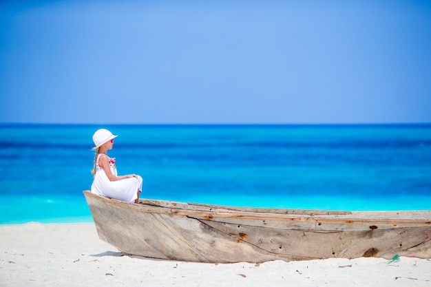 Adorable little girl on boat on the shore