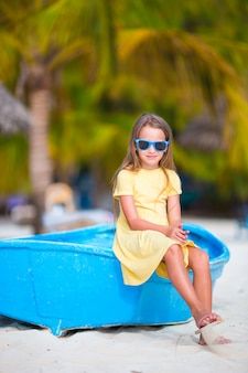 Adorable little girl on boat on white beach