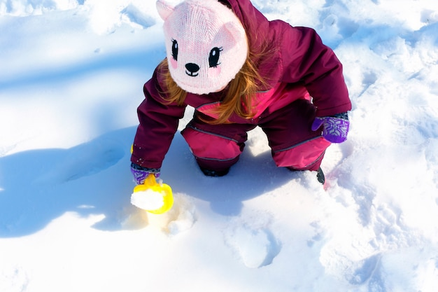 Adorable little girl building a snowman in winter park. cute child playing in a snow