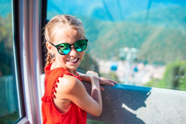 Adorable little girl in the cabin on the cable car in mountains