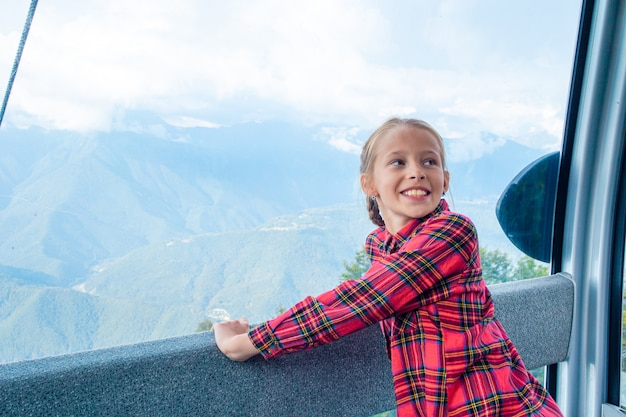Adorable little girl in the cabin on the cable car
