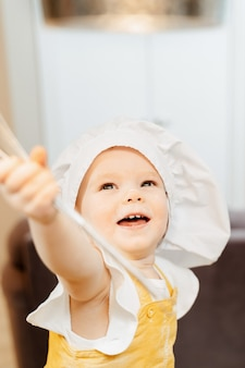 Adorable little girl in a cook hat is holding a whisk in her hands to mix the dough while cooking pasties in the kitchen. the concept of cute curious children doing home work