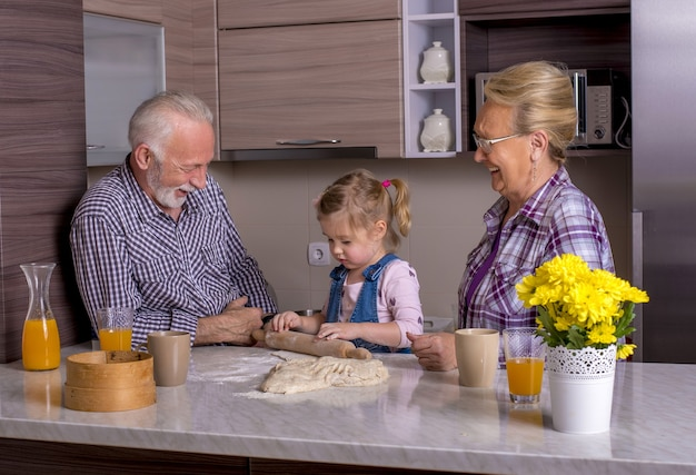 Adorable little girl cooking with her grandparents