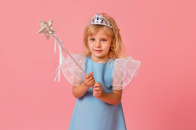 Adorable little girl in costume and wand
