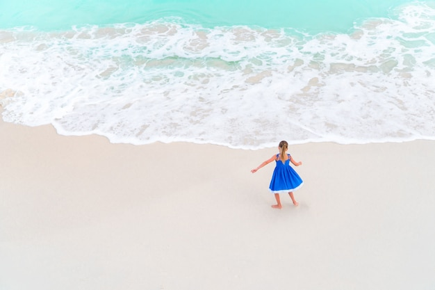 Adorable little girl dancing on white tropical beach. view from above of a deserted beach with turquoise water