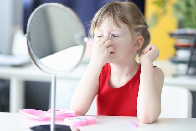 Adorable little girl doing makeup in front of mirror children makeup concept