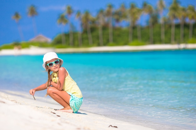 Adorable little girl drawing picture on white beach