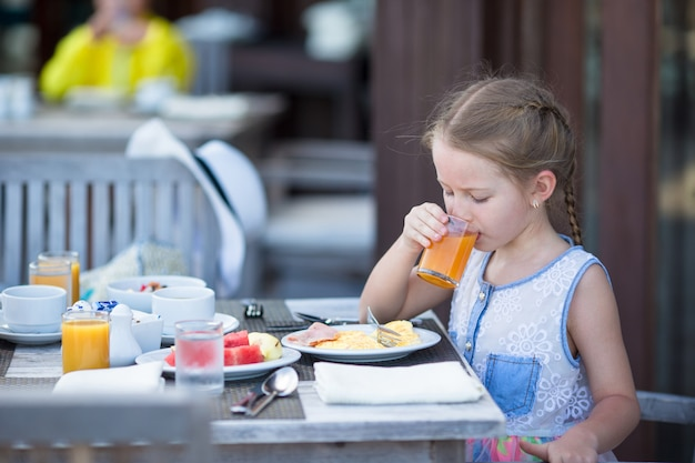 Adorable little girl drinking apple juice for breakfast in outdoor cafe