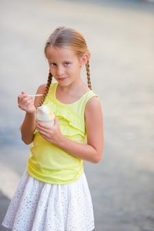 여름에 야외에서 아이스크림을 먹는 사랑스러운 작은 소녀. 로마의 gelateria 근처에서 진짜 이탈리아 젤라토를 즐기는 귀여운 꼬마
