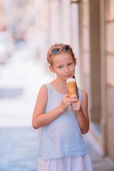 夏に屋外でアイスクリームを食べる愛らしい少女。