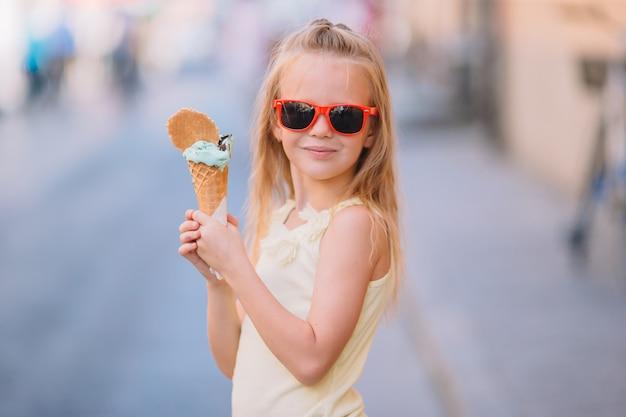 여름에 야외에서 아이스크림을 먹는 사랑스러운 작은 소녀.
