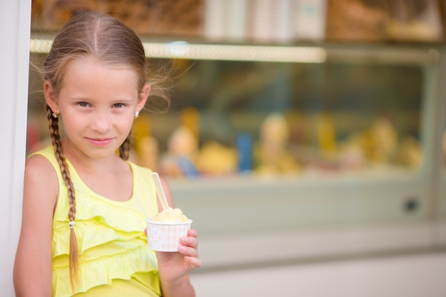 Adorable little girl eating ice-cream outdoors at summer.