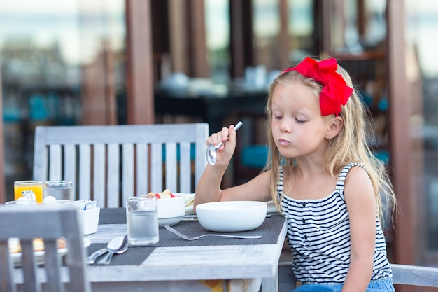 Adorable little girl eating porridge on breakfast at outdoor cafe