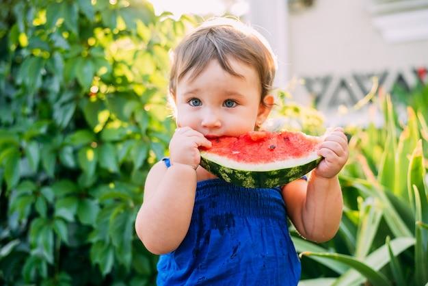 마당에서 수박을 먹는 사랑스러운 어린 소녀
