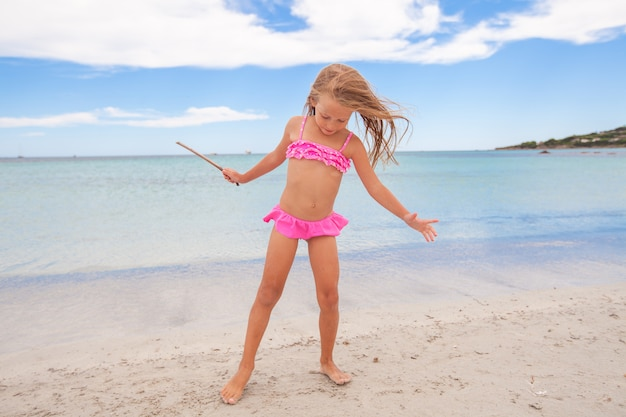 Adorable little girl enjoying tropical beach vacation