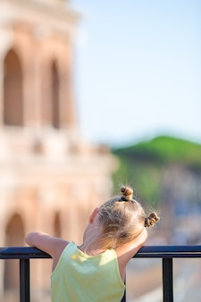 Adorable little girl in front of colosseum in rome, italy.