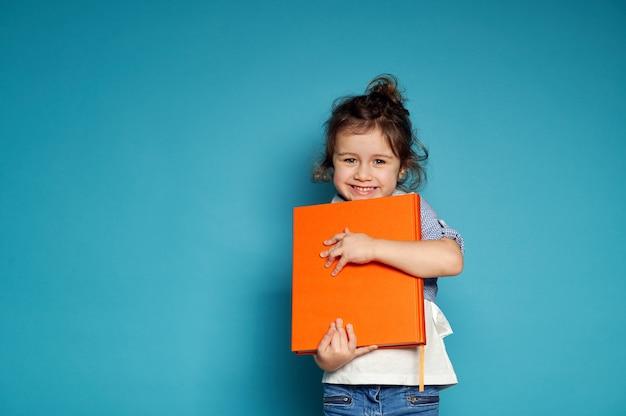Очаровательная маленькая девочка нежно обнимает свою оранжевую книгу и мило улыбается с зубастой улыбкой, глядя вперед, стоя на синей поверхности с копией пространства