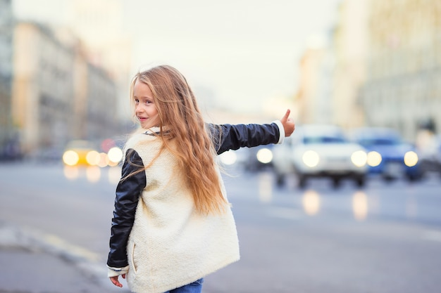 Adorable little girl get taxi outdoors in european city