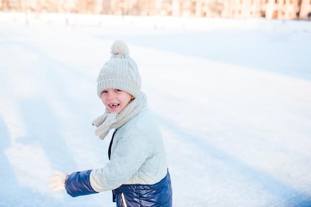 Очаровательная маленькая девочка собирается кататься на коньках в зимний снежный день на открытом воздухе