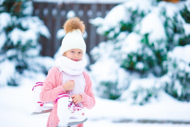 Очаровательная маленькая девочка собирается кататься на коньках на катке в зимний снежный день