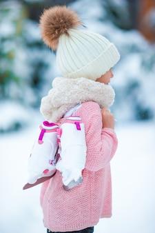 Очаровательная маленькая девочка катается на коньках в зимний снежный день на открытом воздухе