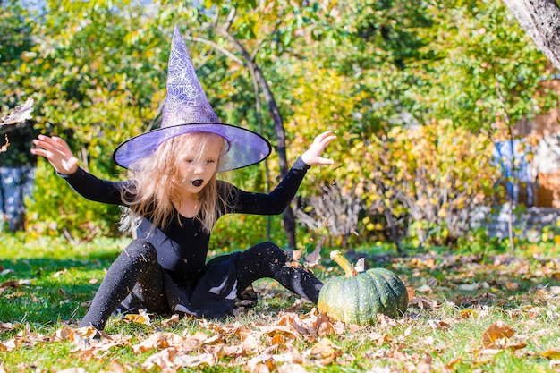 Adorable little girl in halloween which costume having fun outdoors
