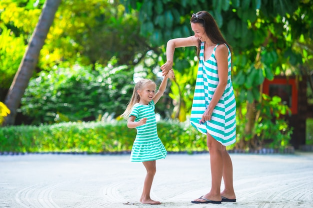 Adorable little girl and happy mom during tropical beach vacation