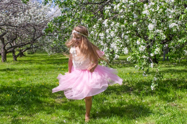 Adorable little girl have fun in blossoming apple orchard