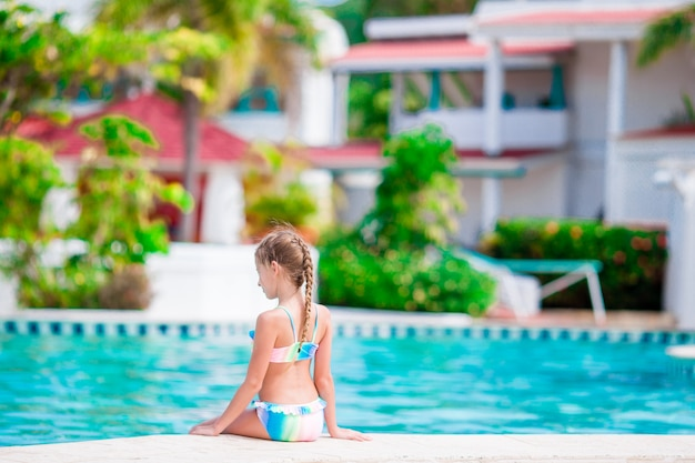 Adorable little girl have fun near swimming pool outdoors