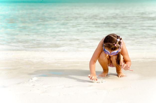 Очаровательная маленькая девочка развлекается на пляже