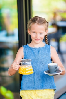 Adorable little girl having breakfast at cafe early in the morning