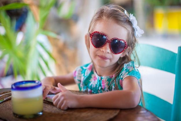 Adorable little girl having breakfast and drinking fruit cocktail