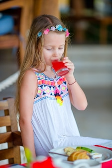 Adorable little girl having breakfast at outdoor cafe. lid drinling fresh juice