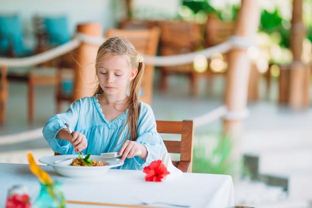 屋外カフェで夕食を食べているかわいい女の子