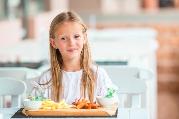 Adorable little girl having dinner at outdoor cafe