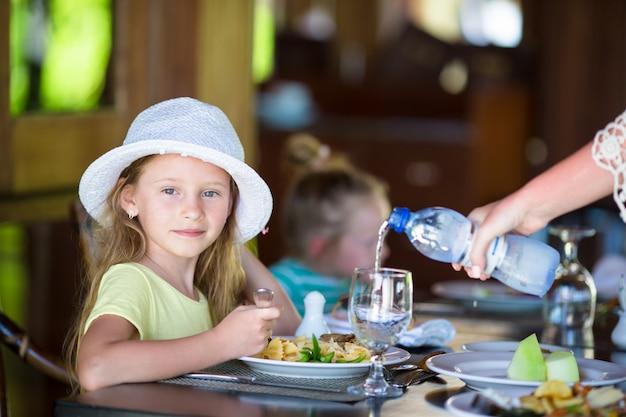 Adorable little girl having dinner at outdoor restaurant