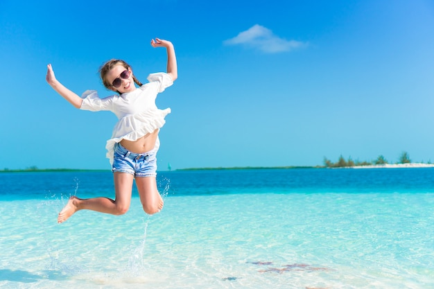 Adorable little girl having fun on the beach full of starfish on the sand
