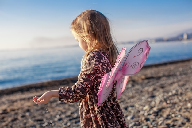 Adorable little girl having fun on the beach in a winter sunny day
