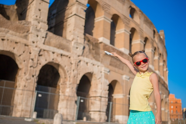 Adorable little girl having fun on colosseum in rome, italy.