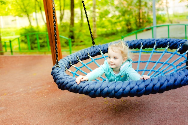 Adorable little girl having fun on a round rope swing in a playground.