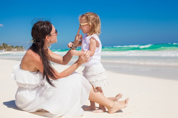 Adorable little girl having fun with her young mother on the white sandy beach in tulum, mexico