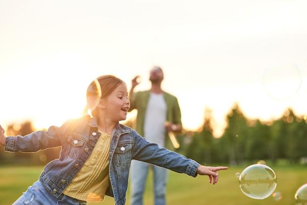 Очаровательная маленькая девочка с мыльными пузырями в солнечный день, дочь и папа, проводящие время