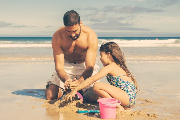 Adorable little girl and her dad building sandcastle on beach, sitting on wet sand, enjoying vacation