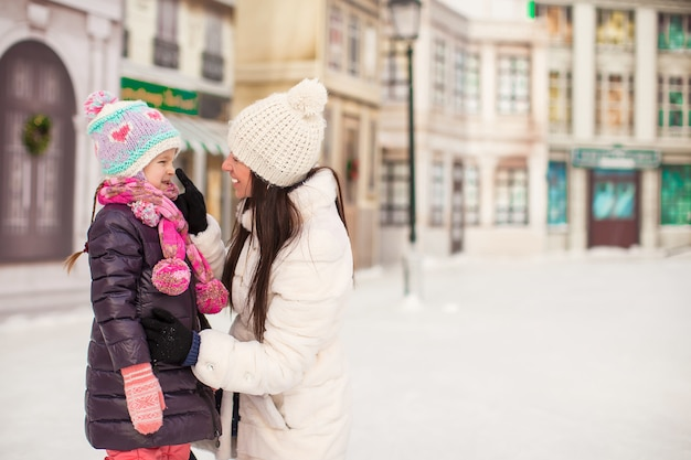 Adorable little girl and her young mother on a skating rink