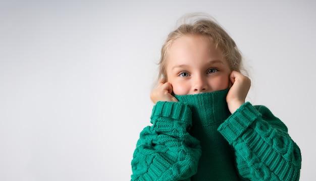따뜻한 니트 스웨터의 두꺼운 칼라 아래에 그녀의 얼굴의 아래 부분을 숨기는 사랑스러운 작은 소녀.