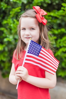 Adorable little girl holding american flag outdoors on beautiful summer day